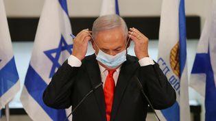 Le Premier ministre israélien, Benyamin Nétanyahou, enfile un masque, le 8 septembre 2020, à Beit Shemesh (Israël). (ALEX KOLOMIENSKY / AFP)