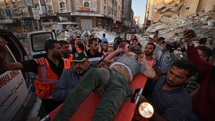 Des Palestiniens transportent un survivant sous les décombres d'un bâtiment, après qu'il ait été frappé par des frappes israéliennes, dans la ville de Gaza, le 16 mai 2021. (MOHAMMED ABED / AFP)