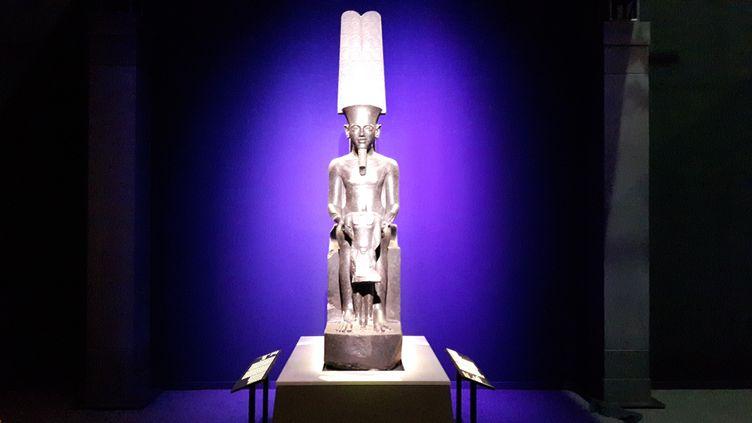 """La statue du Dieu Amon prêtée par le musée du Louvre accueille les visiteurs à l'entrée de l'exposition """"Toutânkhamon, le trésor du Pharaon"""" à la Grande Halle de La Villette à Paris. (ANNE CHÉPEAU / FRANCE-INFO)"""