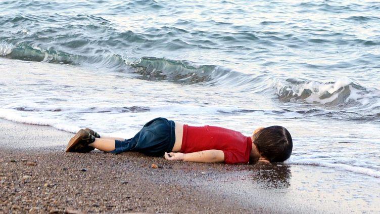 Aylan Kurdi, un enfant syrien de 3 ans, gît sur une plage à Bodrum (Turquie), après le naufrage de son embarcation à destination de l'île de Kos (Grèce), le 2 septembre 2015. (NILUFER DEMIR / DOGAN NEWS AGENCY / AFP)