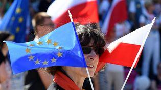 Une manifestante avec le drapeau de l'Union européenne et de la Pologne lors de la Marche de la liberté à Varsovie, le 12 mai 2018. (JANEK SKARZYNSKI / AFP)