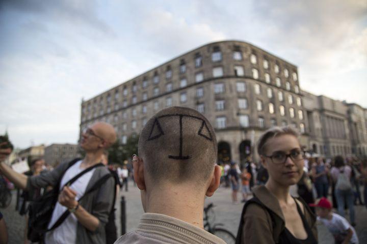 Une femme a peint sur son crâne la balance de la justice pour protester contre la réforme du système judiciaire polonais, le 25 juillet 2017 à Varsovie. (MACIEJ LUCZNIEWSKI / NURPHOTO)