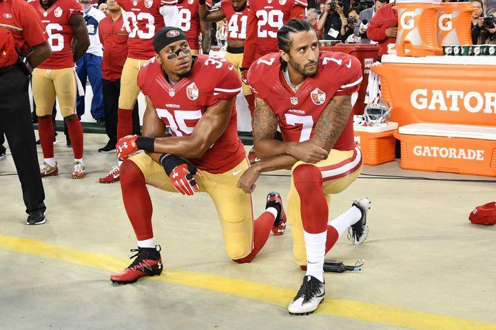 Les joueursde football américain Eric Reid et Colin Kaepernick s'agenouillent durant l'hymne national, le 12 septembre 2016, avant un match entre San Francisco et Los Angeles à Santa Clara (Californie). (THEARON W. HENDERSON / GETTY IMAGES NORTH AMERICA / AFP)