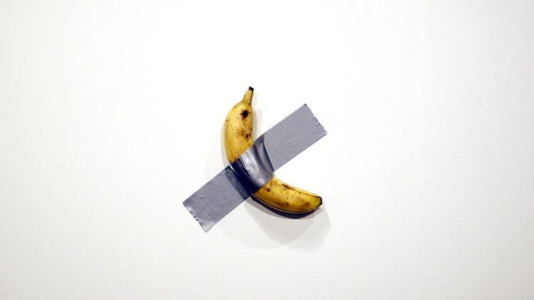 """""""Comedian"""", oeuvre de Maurizio Cattelan, a été tout simplement mangée par un autre artiste,David Datuna. Un quart d'heure plus tard,une nouvelle banane était scotchée au mur. (RHONA WISE / EPA)"""