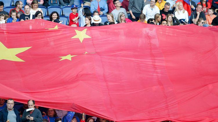 Les supporters chinois arborent un drapeau géant de la Chine lors du match de football du groupe B de la Coupe du monde féminine entre l'Afrique du Sud et la Chine, au stade du Parc des Princes à Paris, en 2019.   (J.E.E/SIPA)
