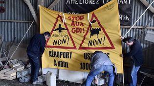 """Des opposants au projet d'aéroport de Notre-Dame-des-Landes (Loire-Atlantique) installent une banderole, avant la visite de la direction d'EELV, le 4 novembre 2015, à la """"Vache-rit"""". (GEORGES GOBET / AFP)"""