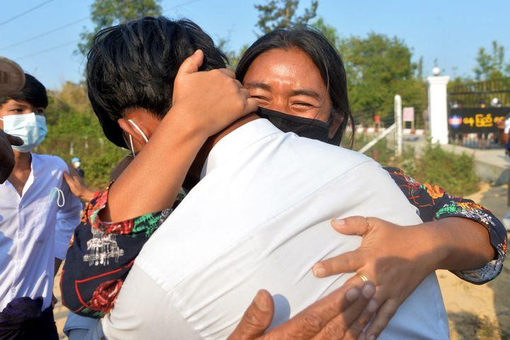 Une femme birmane prend dans ses bras un jeune membre de sa famille, étudiant, qui vient d'être relâché après avoir été détenu à Naypyidaw (Birmanie), le 15 février 2021. (STR / AFP)