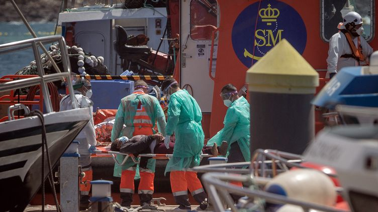 Une femme qui avait tenté de rejoindre les Canaries est secourue par du personnel soignant sur l'île de Tenerife (Espagne), le 26 mars 2021. (DESIREE MARTIN / AFP)