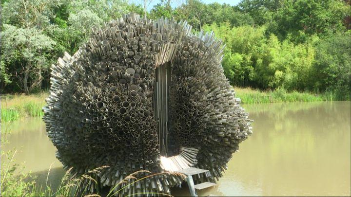 La Sidérolithe est une sculpture-habitacle en tubes d'acier inox, conçue en 1995 et achevée en 2001. Dimensions: H 6m et diamètre 8 m.Placée sur un miroir d'eau, elle est conservée à l'atelier de l'artiste à Aurouër (Allier). (C. Darneuville / France Télévisions)