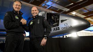 Bertrand Piccard et André Borschberg posent devant l'avion solaire Solar Impulse 2, le 9 avril 2014 à Payerne (Suisse). (FABRICE COFFRINI / AFP)