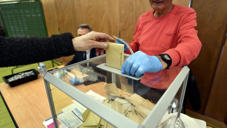 Un assesseur porte des gants dans un bureau de vote à Essey-lès-Nancy. (ALEXANDRE MARCHI / MAXPPP)
