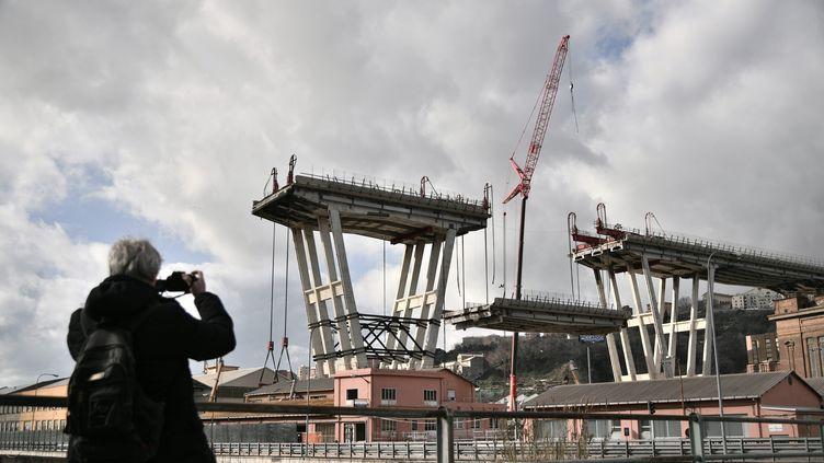 Une personne prend une photo du démarrage du démontage du pont Morandi, à Gênes, en Italie. (MARCO BERTORELLO / AFP)