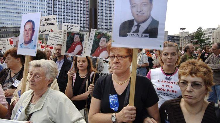 """Une vingtaine de """"veuves de Dunkerque"""" défilent, le 30 septembre 2006 à Paris, en tête d'une manifestation de plusieurs milliers de personnes pour réclamer un grand """"procès pénal de l'amiante"""" et une meilleure indemnisation des victimes.  (ERIC FEFERBERG / AFP)"""