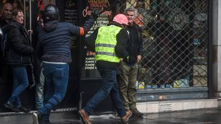 Un policier en civil avec sa matraque télescopique court après un manifestant, le 1er décembre 2018, à Paris. (LUCAS BARIOULET / AFP)