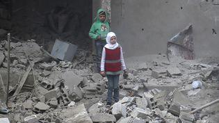 Des enfants dans les ruines d'Hamouria dans la Ghouta orientale en Syrie, le 22 février 2018. (ABDULMONAM EASSA / AFP)