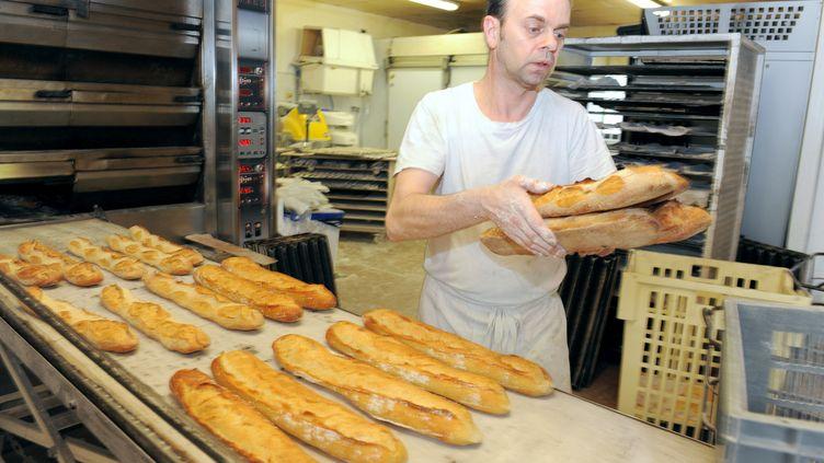 Un boulanger sort des baguettes du four, le 11 mai 2015, à Quimper (Finistère). (FRED TANNEAU / AFP)