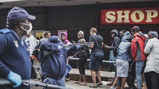 Intervention de la police sud-africaine, le 28 mars 2020, pour faire respecter les règles de distanciation sociale, dans une file de clients agglutinés devant un supermarché de Johannesburg. (MARCO LONGARI / AFP)
