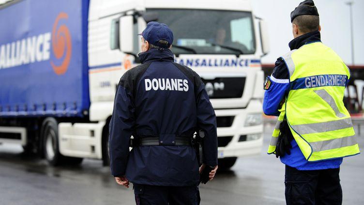 Un agent des douanes françaises et un gendarme surveillent les véhicules qui traversent Gye (Meurthe-et-Moselle), le 26 avril 2013. (JEAN-CHRISTOPHE VERHAEGEN / AFP)