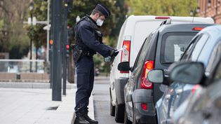 Un fonctionnaire de police contrôle un automobiliste, à Toulouse (Haute-Garonne), mercredi 8 avril 2020. (FREDERIC SCHEIBER / HANS LUCAS / AFP)