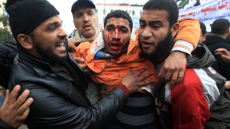 Des Égyptiens aident un manifestant lors d'affrontements entre pro et anti-Mohamed Morsi, le 21 décembre 2012 à Alexandrie (Egypte). (MAHMUD HAMS / AFP)