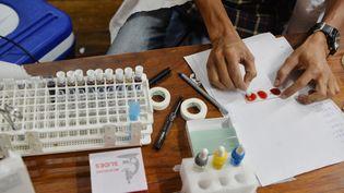 Un responsable d'une banque de sang indienne teste une lame recouverte d'un échantillon de sang alors qu'il vérifie le groupe sanguin d'un donneur à Salugara Monestry,près de Siliguri, le 10 mai 2019. (DIPTENDU DUTTA / AFP)
