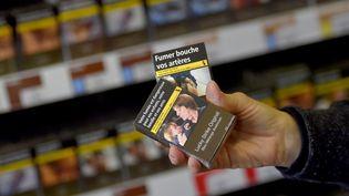 Une personnetenant des paquets de cigarettes dans un bureau de tabac à Vertou (Loire-Atlantique), le 27 décembre 2016. (LOIC VENANCE / AFP)