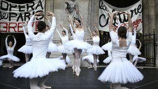 """Des danseuses de l'Opéra de Paris interprètent un tableau du """"Lac des cygnes"""" sur le parvis du palais Garnier, le 24 décembre 2019. (STEPHANE DE SAKUTIN / AFP)"""