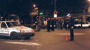 Un policier examine la voiture de police impliquée dans la poursuite et la fusillade qui a fait 5 morts dans la nuit du 4 au 5 octobre 1994, à Paris. (MARIO GOLDMAN / AFP)
