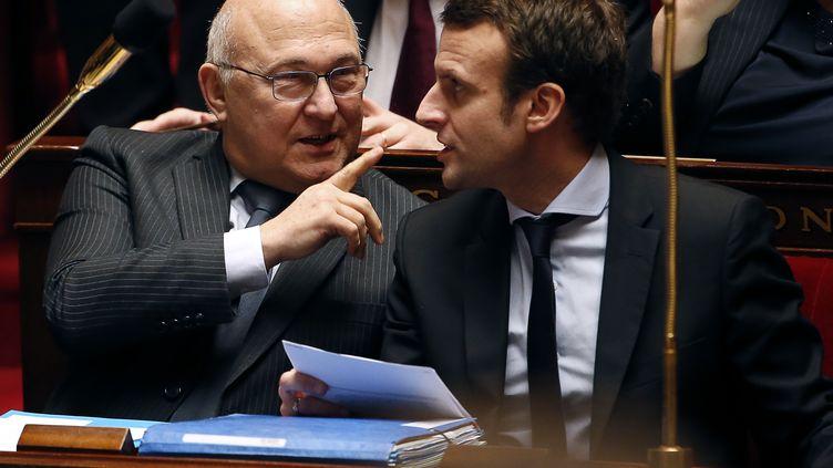 Michel Sapin (à gauche) et Emmanuel Macron, le 17 mai 2016 sur les bancs del'Assemblée nationale. (THOMAS SAMSON / AFP)