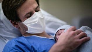 Un père tient son fils peu après sa naissance, le 17 novembre 2020, à la maternité des Diaconesses, à Paris. (MARTIN BUREAU / AFP)