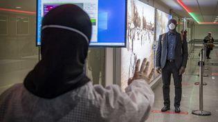 Des agents de santé marocains scannent les passagers en provenance d'Italie à la recherche du coronavirus à l'aéroport international Mohammed V de Casablanca, le 3 mars 2020. (FADEL SENNA / AFP)