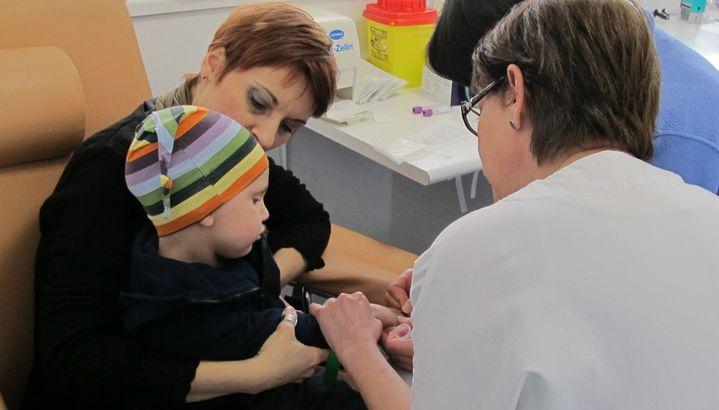Une infirmière effectue un prélèvement sanguin pour Enzo, atteint d'une tumeur au cerveau, ici sur les genoux de sa mère, le 19 février 2013. (MARION SOLLETTY / FRANCETV INFO)