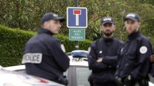 Des policiers sont réunis à Magnanville, dans les Yvelines, le 14 juin 2016 près du domiciled'un couple de policiers tués la veille.  (THOMAS SAMSON / AFP)