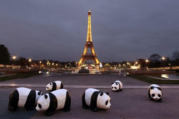 """Des pandas en papier mâché installés par l'association WWF pour sensibiliser le public à l'opération """"Une heure sans lumière"""", le 31 mars 2012 à Paris. (KENZO TRIBOUILLARD / AFP)"""