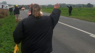 (Au bord de la route, Aurélie salue la caravane pour avoir quelques cadeaux © RF/BS)