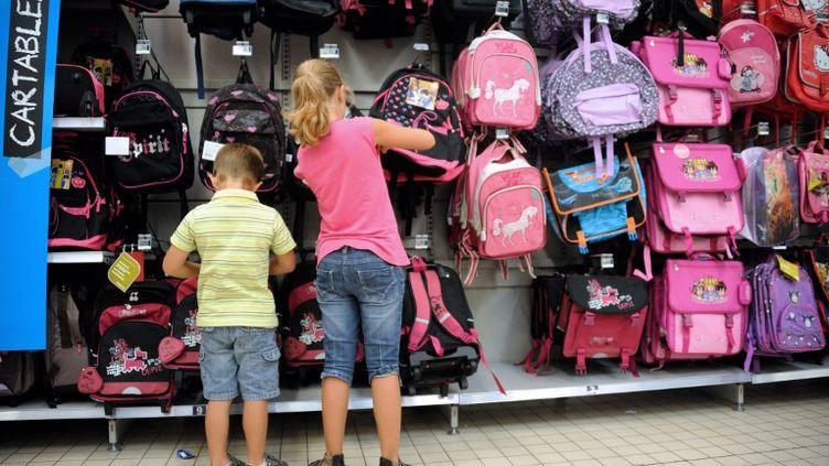 Des enfants regardent des cartables dans le rayon d'un supermarché à Englos (Nord), le 22 août 2012. (PHILIPPE HUGUEN / AFP)