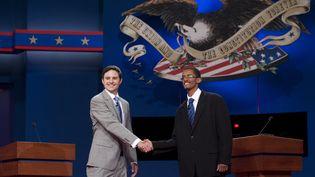 Deux étudiants de l'université de Denver (Etats-Unis) répètent la poignée de mains qui doit ouvrir le débat entre Barack Obama et Mitt Romney, à Denver, le 2 octobre 2012. (SAUL LOEB / AFP)