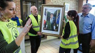 Des militants d'ANV-COP21 décrochent un portrait d'Emmanuel Macron à la mairie de Cabestany (Pyrénées-Orientales), le 27 février 2019. (RAYMOND ROIG / AFP)