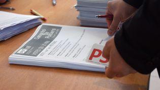 Un militant PS s'empare d'un bulletin, le 21 mai 2015, dans un bureau de Lille (Nord) lors du vote sur les motions. (DENIS CHARLET / AFP)