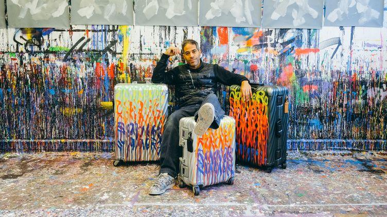 Le street artiste JonOne pose au milieu de valises de la marque Tumi revisitées de splashs de couleurs. Février 2020 (©TOINE. TOINEBEHIND.COM)