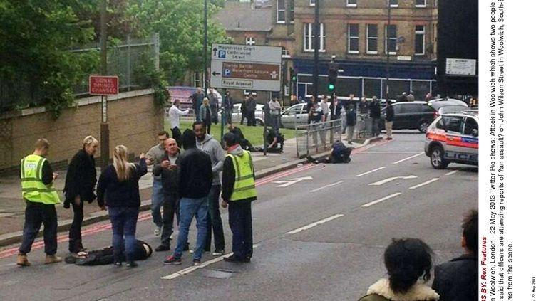 Les policiers sur les lieux du crime, le 22 mai 2013, à Woolwich, quartier de Londres. Au premier plan, le corps d'un homme égorgé, tandis que la police interpelle les deux agresseurs présumés au second plan. (REX FEATURES/SIPA)