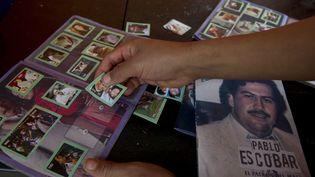 Un garçon colle des images dans un album d'images dédié à Pablo Escobar, à Medellin (Colombie), le 8 août 2012. (RAUL ARBOLEDA / AFP)