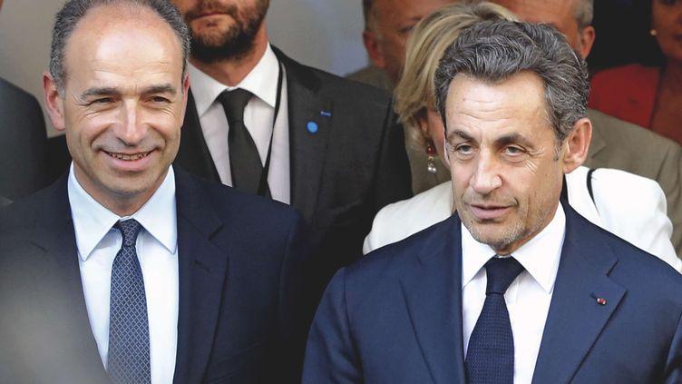 Le président de l'UMP, Jean-François Copé, et l'ancien chef de l'Etat, Nicolas Sarkozy, sortent du siège de l'UMP, le 8 juillet 2013 à Paris. (JACQUES BRINON / AP / SIPA)