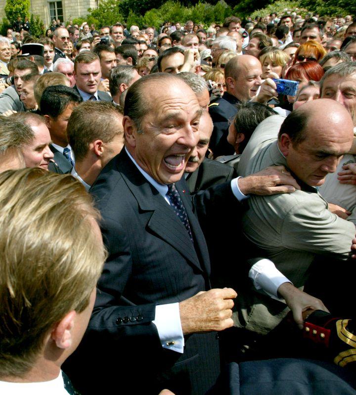 Leprésident de la République Jacques Chirac prend un bain de foule, le 14 juillet 2002,pendant la traditionnelle garden party au palais de l'Elysée, à Paris. (PATRICK KOVARIK / AFP)