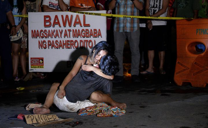 Jennilyn Olayres et le corps de son compagnon,Michael Siaron, abattu dans une rue de Manille (Philippines), le 23 juillet 2016. (NOEL CELIS / AFP)