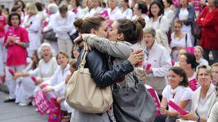 """Deuxjeunes femmes s'embrassent devant des personnes participant à une manifestation de l'association """"Alliance Vita"""" contre le mariage et l'adoption par des couples homosexuels, le 23 octobre 2012 à Marseille (Bouches-du-Rhône). Le cliché a eu un important retentissement, au point d'être baptisé """"Le Baiser de Marseille"""". (GERARD JULIEN / AFP)"""