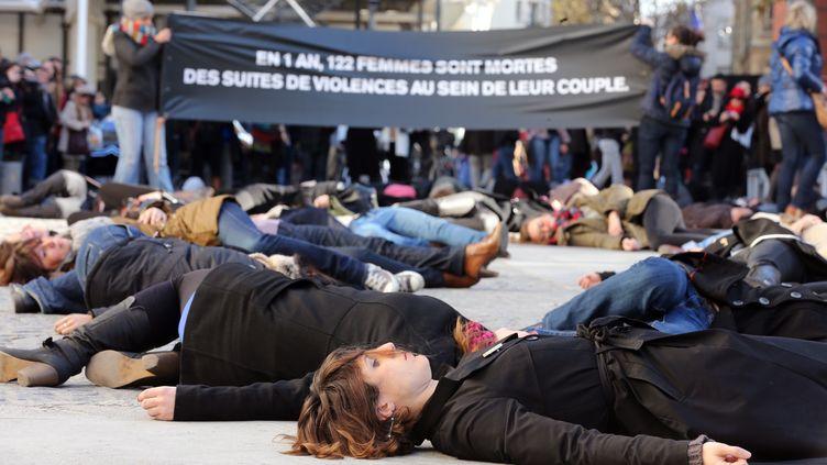 Des femmes s'allongent sur le sol pour dénoncer les violences subies par les femmes de la part de leur conjoint, lors d'une manifestation à Paris en novembre 2012. (THOMAS SAMSON / AFP)