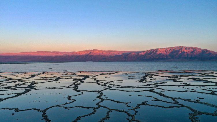 Des minéraux cristallisés forment des motifs à la surface des bassins d'évaporation de la mer Morte, près du village de Neve Zohar, dans le sud d'Israël. (MENAHEM KAHANA / AFP)