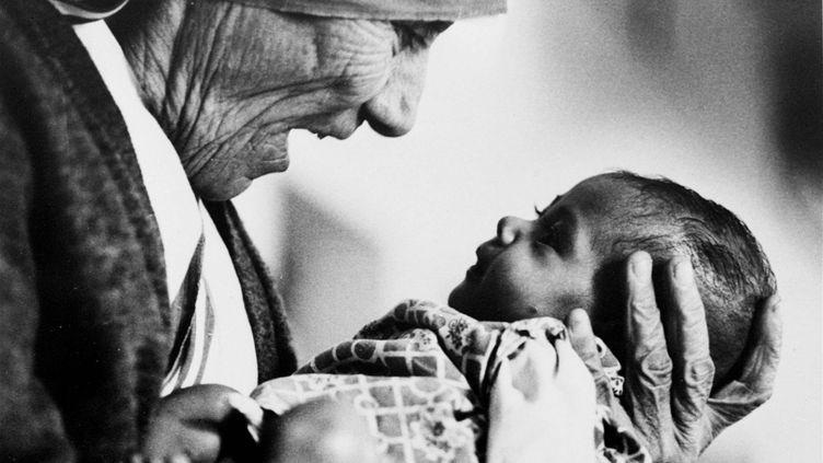 Mère Teresa, prix Nobel de la paix, photographiée ici avec une jeune orpheline dans les bras, à Calcutta (Inde), en 1978. (EDDIE ADAMS / AP / SIPA)