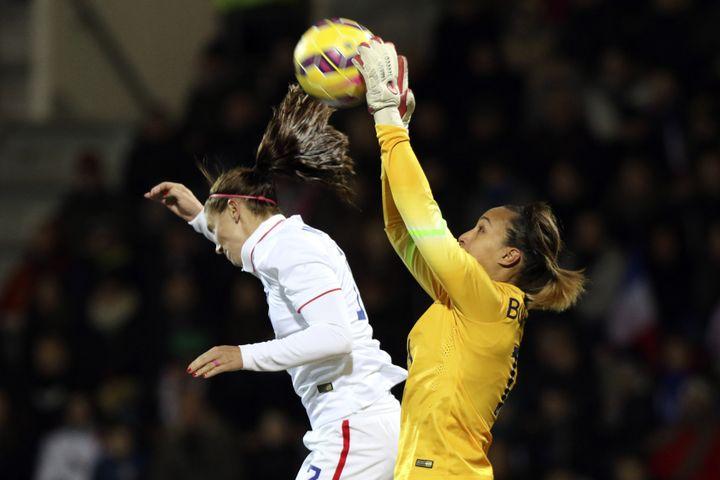 La gardienne de l'équipe de France, Sarah Bouhaddi (en jaune), s'empare du ballon face à l'Américaine Tobin Heath, lors d'un match amical, le 8 février 2015 au stade du Moustoir de Lorient. (EDDY LEMAISTRE / 2PIX-EL)